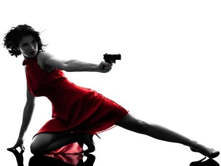 白い背景で隔離のシルエット スタジオで銃を保持している 1 つのセクシーな白人女性