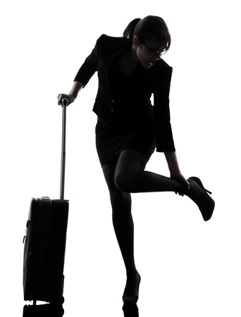 one business woman traveling massaging feet  silhouette studio isolated on white background photo