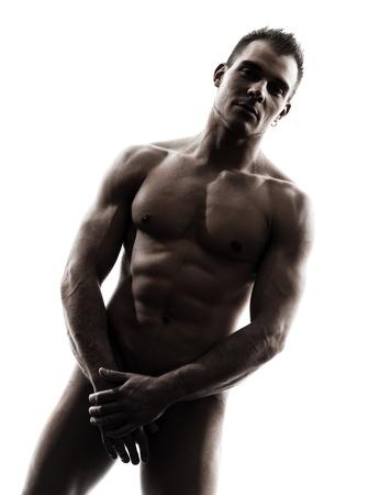 hombre desnudo: un guapo muscular nanómetro retrato del hombre caucásico de pie en el estudio de la silueta sobre fondo blanco Foto de archivo