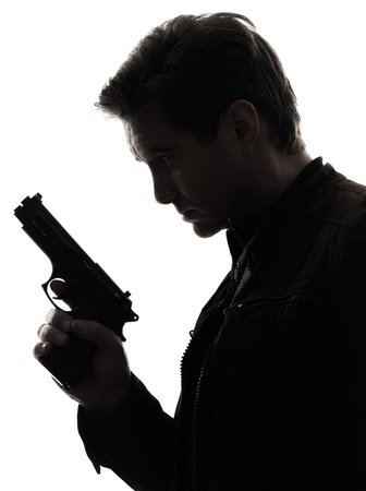 one man killer policeman holding gun portrait silhouette studio white background Stock Photo