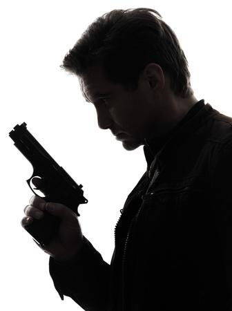 pistolas: un hombre polic?a asesino sosteniendo la pistola retrato silueta white background Foto de archivo