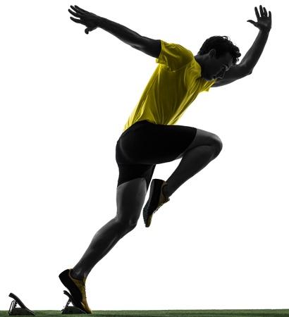 starting blocks: one caucasian man young sprinter runner  in starting blocks  silhouette studio  on white background