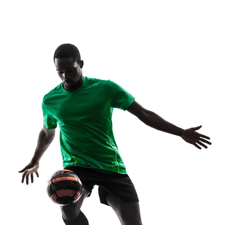 indoor soccer: one african man soccer player green jersey juggling in silhouette  on white background