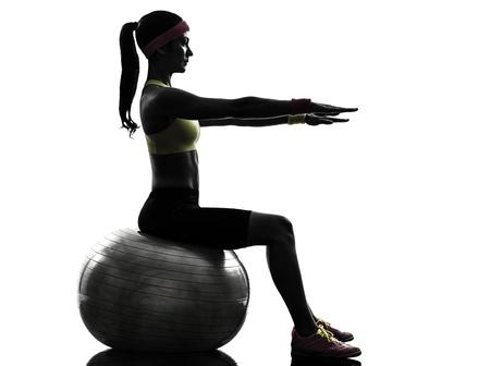 一人の女性は白い背景にシルエット フィットネス ボールでフィットネス トレーニングを行使 写真素材