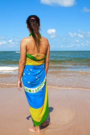 woman with the brazilian flag sarong on the beach looking at the sea Stock Photo