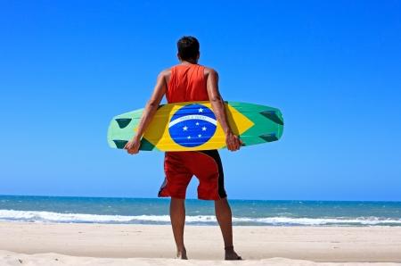 Kite surfer with the brazilian flag painted on the board with praia e vento (beach and wind) instead of ordem e progresso  in prainha beach near fortaleza