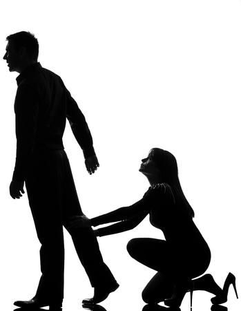 divorcing: one caucasian couple dispute separation man leaving and woman holding back in studio silhouette isolated on white background