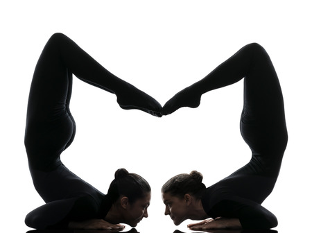 two floors: two women contortionist practicing gymnastic yoga in silhouette   on white background Stock Photo