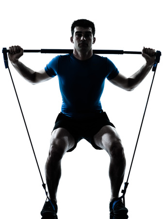 crouches: one caucasian man exercising workout fitness in silhouette studio  isolated on white background