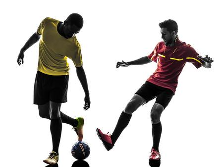 playing football: jugador de f�tbol de dos hombres jugando competici�n de f�tbol en silueta sobre fondo blanco Foto de archivo