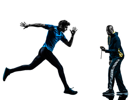 athleticism: one caucasian man  running sprinting with coach stopwatch in silhouette studio isolated on white background