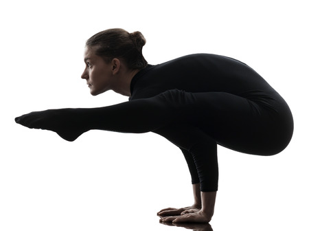 yoga silhouette: one caucasian woman contortionist practicing gymnastic yoga  in silhouette   on white background