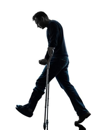 one  man injured man walking sad with crutches in silhouette studio  on white background photo