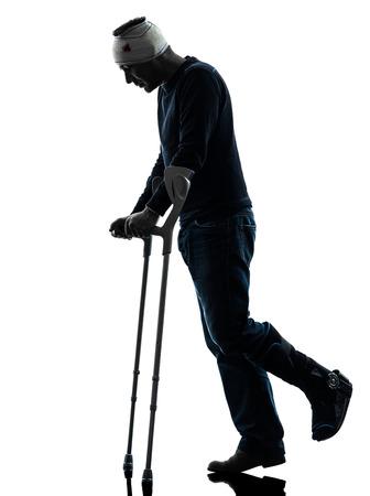 lesionado: un hombre herido camina triste con muletas en estudio de la silueta sobre fondo blanco