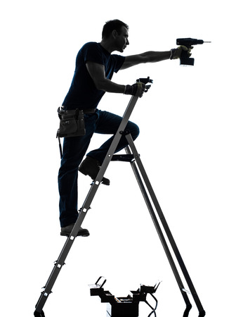 one  manual worker man standing on ladder drilling  in silhouette on white background photo