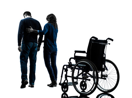 one  man with woman  walking away from  wheelchair  in silhouette studio  on white background photo