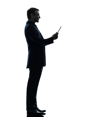 one caucasian business man smiling  holding digital tablet   in silhouette on white background photo