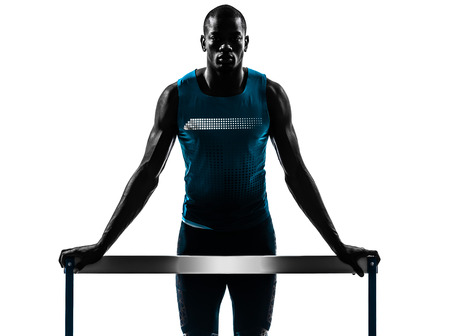 one african man hurdler runner standing in silhouette studio isolated on white background photo