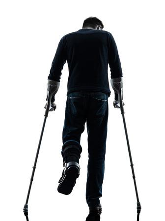 ein Mann verletzte Mann, der mit Krücken Rückansicht in der Silhouette Studio auf weißem Hintergrund