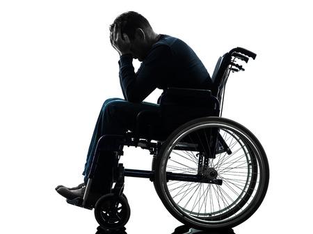 een gehandicapte man, hoofd in handen in silhouet studio op een witte achtergrond