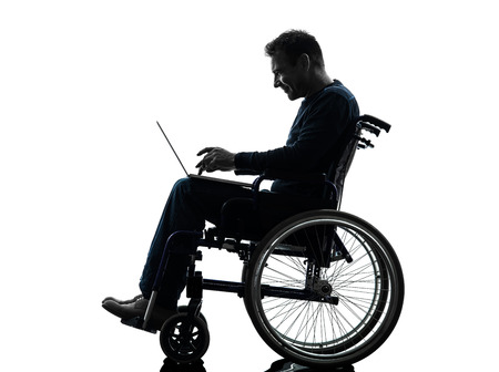 one handicapped man computing laptop computer in silhouette studio  on white background photo