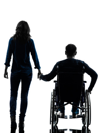 men back: one handicapped man and woman holding hands in silhouette studio  on white background