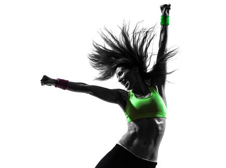 una mujer caucásica que ejercita aptitud del zumba baile en la silueta en el fondo blanco