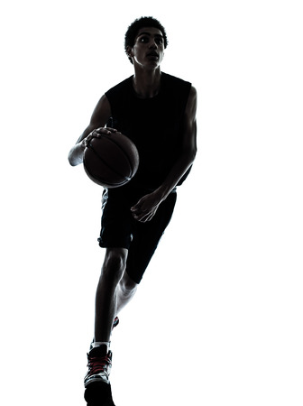 one young man basketball player dribbling silhouette in studio isolated on white background photo