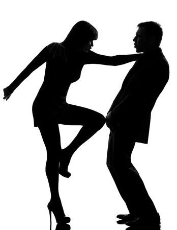 self defense: one caucasian couple man and woman expressing domestic violence in studio silhouette isolated on white background Stock Photo