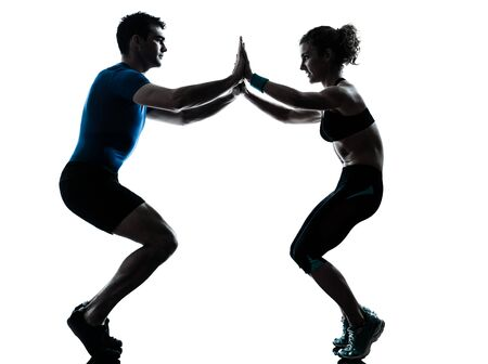 one caucasian couple man woman personal trainer coach exercising squats silhouette studio isolated on white background photo