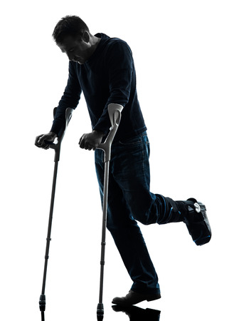 silueta masculina: un hombre herido camina con muletas en estudio de la silueta sobre fondo blanco