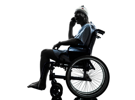 one  injured man on the telephone surprised in wheelchair  in silhouette studio  on white background photo