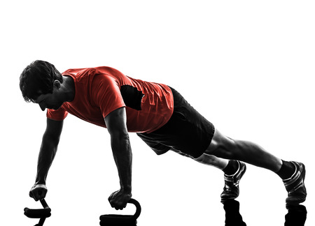 push ups: one  man exercising fitness workout push ups  in silhouette  on white background