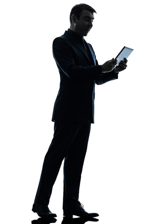 one caucasian business man surprised  holding digital tablet   in silhouette on white background photo