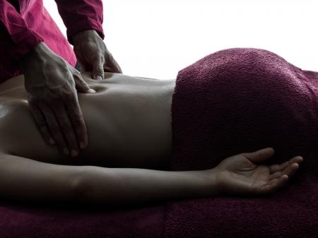 masajes relajacion: mujer hombre masaje de espalda en el estudio de la silueta en el fondo blanco Foto de archivo