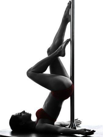 dancers: one caucasian woman pole dancer dancing in silhouette studio isolated on white background