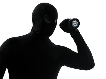 thief criminal with flashlight in silhouette studio isolated on white background photo