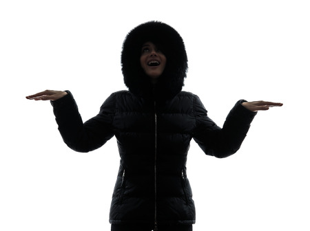 parka: one  woman in winter coat  arms outstretched happy silhouette on white background