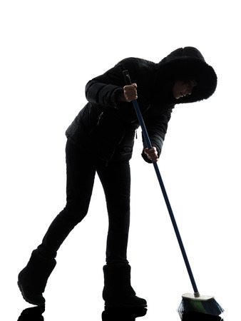 brooming: one  woman in winter coat  brooming silhouette on white background