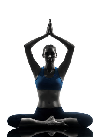yoga: one caucasian woman exercising yoga meditating sitting hands joined in silhouette studio isolated on white background
