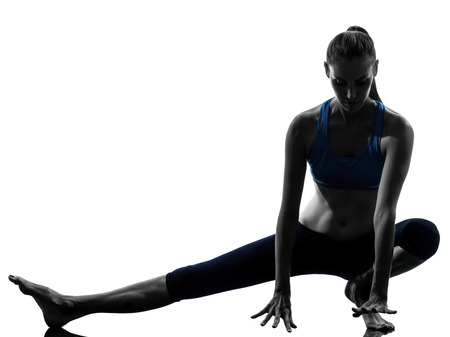 warm up: one caucasian woman exercising yoga stretching legs warm up in silhouette studio isolated on white background