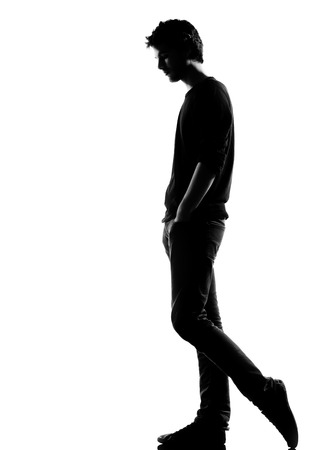 young man sad walking silhouette in studio isolated on white background photo