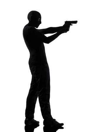 thief criminal terrorist man aiming gun in silhouette studio isolated on white background photo
