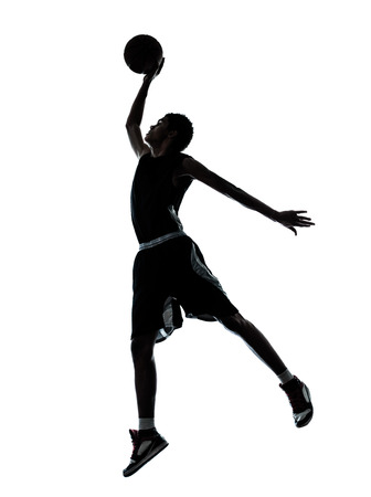 one young man basketball player dunking silhouette in studio isolated on white background