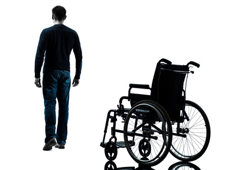 one man: one man walking away from wheelchair in silhouette studio on white background Stock Photo