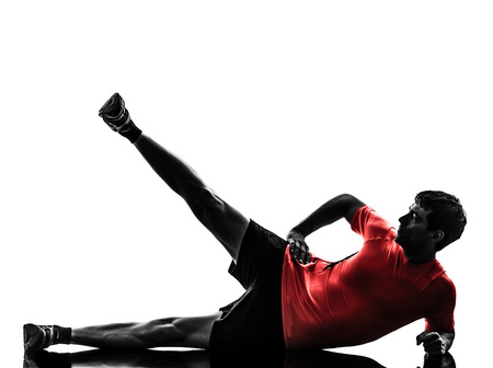 one man: one  man exercising fitness workout legs in the air lying on side in silhouette  on white background