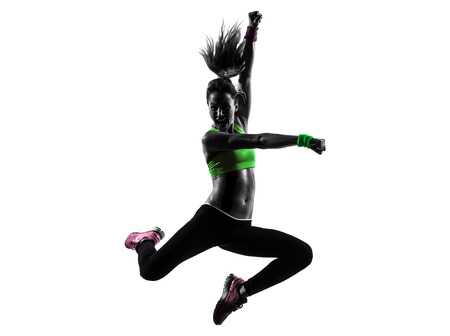 one caucasian woman exercising fitness zumba dancing jumping in silhouette  on white background Stock Photo