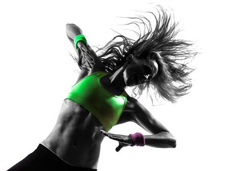zumba: una mujer caucásica que ejercita aptitud del zumba baile en la silueta en el fondo blanco Foto de archivo