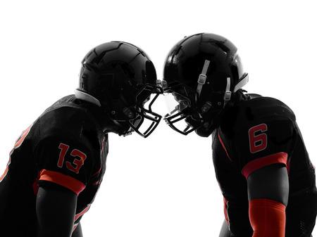 uniforme de futbol: dos jugadores de f�tbol americano de cara a cara en la sombra de la silueta en el fondo blanco Foto de archivo