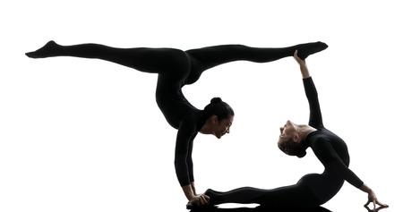 acrobacia: dos mujeres contorsionista practicar yoga gimnasia en silueta sobre fondo blanco